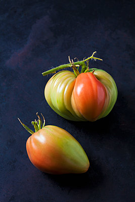 Two Oxheart tomatoes on dark ground - p300m2079006 by Dieter Heinemann