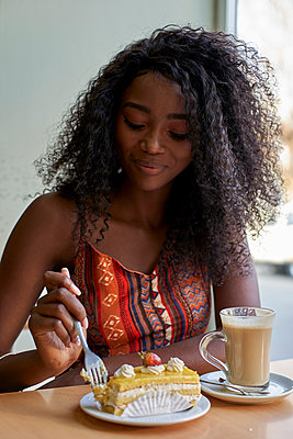 Portrait of young African woman eating a piece of cake and having a coffee - p300m2140731 by Veam