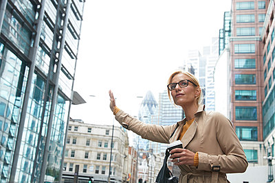 Woman with coffee cup waving hand while standing in city - p300m2227059 by Pete Muller