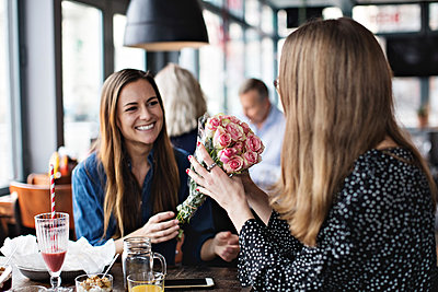 Smiling young woman giving fresh flower bouquet to female friend sitting at restaurant - p426m1570188 by Maskot