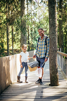 Portrait of father and daughter with picnic basket standing on footbridge in forest - p426m2213163 by Maskot
