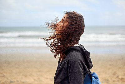 Female tourist with flyaway hair on beach, Las Palmas, Gran Canaria, Canary Islands, Spain - p429m2019098 by Matt Lincoln