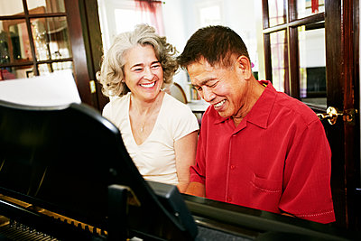 Couple playing piano together in living room - p555m1410202 by Peathegee Inc