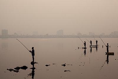 Fishermen on West Lake at dusk in Hanoi, Vietnam, Southeast Asia - p934m1093551f by Aaron Joel Santos