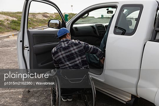 Disabled man in a wheelchair enjoying a day out - p1315m2162380 by Wavebreak