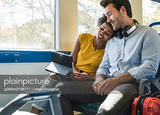 Young couple with tablet relaxing in a train - p300m2156771 by Uwe Umstätter