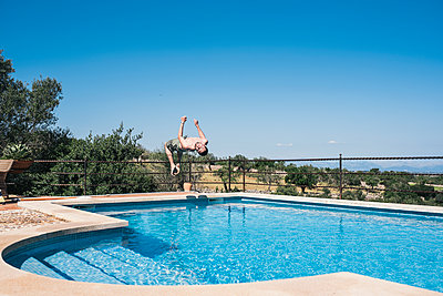 Doing a somersault into the pool - p1046m1467519 by Moritz Küstner