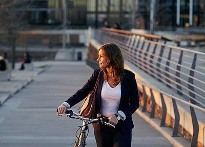 Frau schiebt Fahrrad - p1124m1332964 von Willing-Holtz