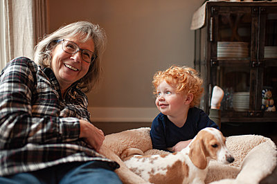 Grandmother and grandson laughing while laying next to puppy at home - p1166m2137723 by Cavan Images