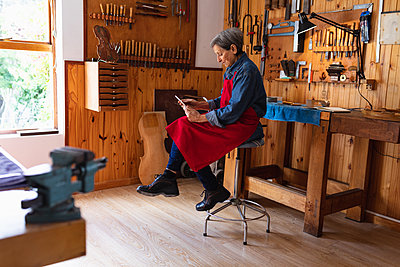 Female luthier using tablet in a workshop - p1315m2131474 by Wavebreak