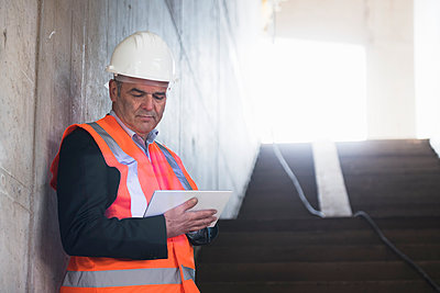 Man with tablet wearing safety vest in building under construction - p300m1460696 by Daniel Ingold