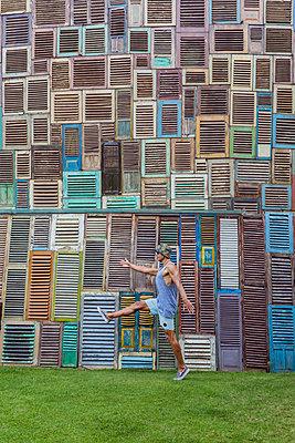 Indonesia, Bali, man walking at wall of wooden windows - p300m2083702 by Konstantin Trubavin