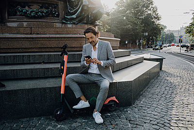 Businessman with e-scooter in the city - p300m2140054 by Johanna Lohr
