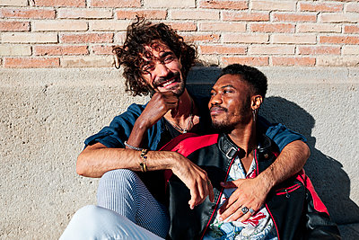 Smiling gay couple sitting in front of brick wall - p300m2287154 by Alvaro Gonzalez