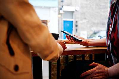 Women holding smart phone sitting at coffee table - p300m2287308 by Angel Santana Garcia
