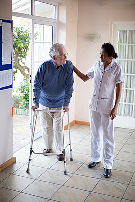 Nurse talking to patient using walker - p555m1305751 by Resolution Productions
