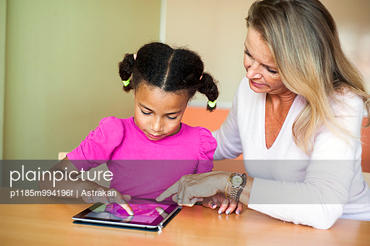 Mature teacher assisting girl in using digital tablet at desk