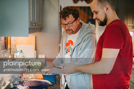 Father and son cooking together in the kitchen - p1507m2220177 by Emma Grann