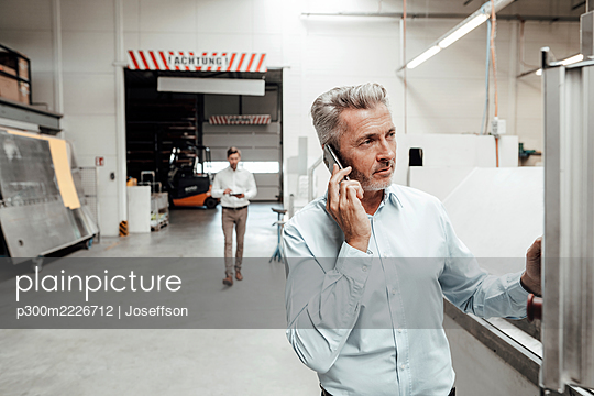 Businessman talking on mobile phone while colleague walking on background at industry - p300m2226712 by Joseffson