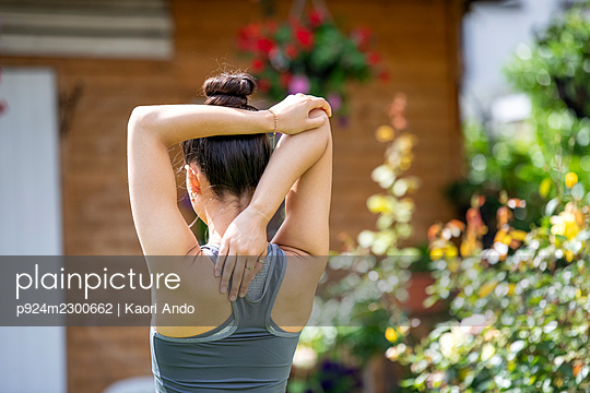 UK, London, Rear view of woman stretching outdoors - p924m2300662 by Kaori Ando