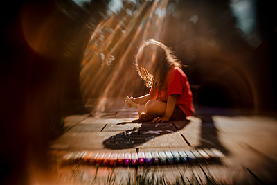 girl drawing with colorful chalks on the patio during a summer evening - p1166m2162863 by Cavan Images