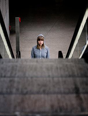 Junge Frau mit Kapuzenjacke auf Rolltreppe im Bahnhof - p1212m1137057 von harry + lidy