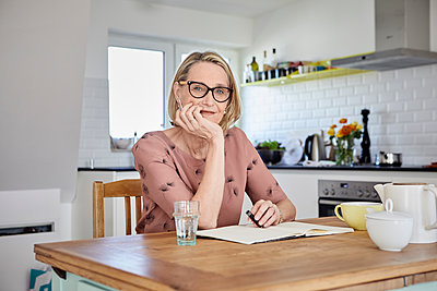 Portrait of mature woman with notebook at kitchen table - p300m1505225 by Rainer Berg