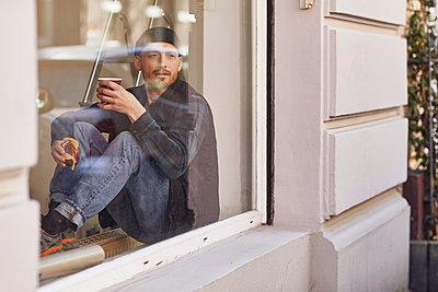Man refurbishing shop location, sitting on windowsill, drinking coffee - p300m2188933 by Maya Claussen
