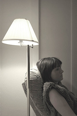 Woman sitting in a chair in a room with a lamp next to her - p3313107 by Gail Symes