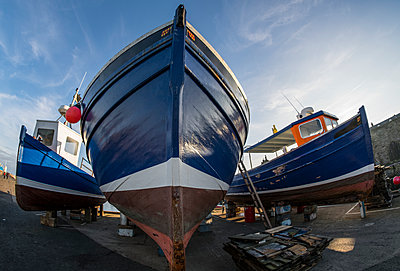 Low angle view of the bow of a fishing boat on the shore for maintenance; Seahouses, Northumberland, England - p442m1482897 by John Short