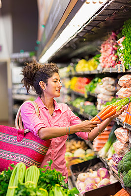 Hispanic woman shopping at grocery store - p555m1411400 by Marc Romanelli