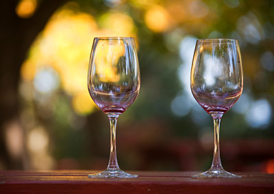 Empty Wine Glasses on Patio Table - p555m1452999 by Spaces Images