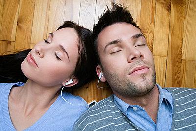 Junges Paar liegt nebeneinander auf Holzboden und hört Musik - p6090285f von CHRIS