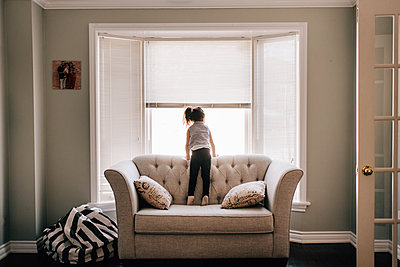 Girl standing on sofa looking through living room window, rear view - p924m2091315 by Sara Monika