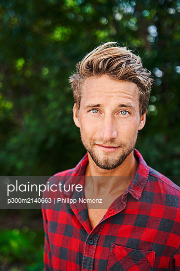 Portrait of confident young man wearing checkered shirt outdoors - p300m2140663 by Philipp Nemenz
