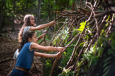 Two girls building a hut in the forest - p1007m2219992 by Tilby Vattard