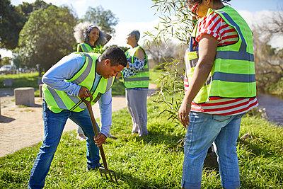 Volunteers planting trees in sunny park - p1023m2066888 by Trevor Adeline