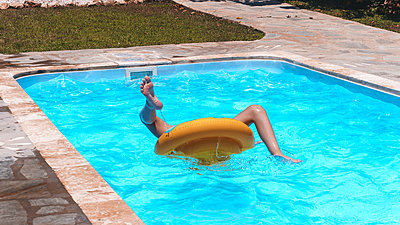 Little girl spinning in the pool - p1166m2159636 by Cavan Images
