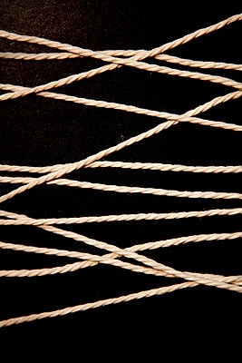 Thick String in front of black background - p1248m2260675 by miguel sobreira