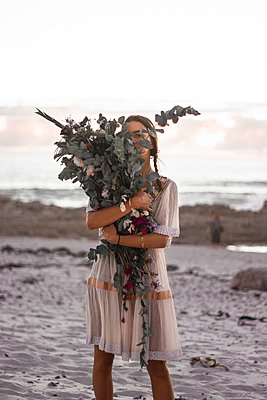 Teenage girl with bunch of flowers on the beach - p1640m2246202 by Holly & John