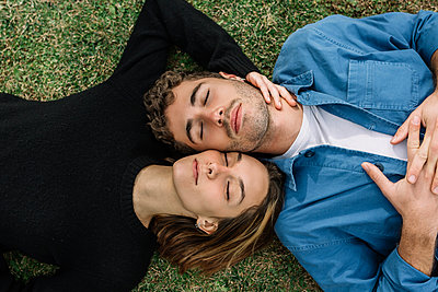 Smiling couple lying on lawn with eyes closed - p300m2256838 by Xavier Lorenzo
