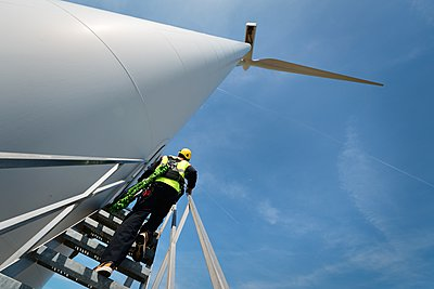Maintenance worker standing on a modern wind turbine, Biddinghuizen, Flevoland, Netherlands - p429m1029812 by Mischa Keijser