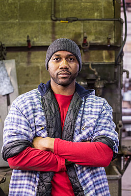 Black worker standing in factory - p555m1312003 by Jetta Productions