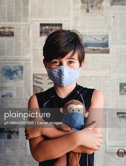 Young boy wearing mask holding toy monkey with newspaper backdrop. - p1166m2201335 by Cavan Images