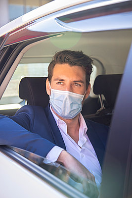 Close-up of businessman wearing face mask looking through window while sitting in taxi - p300m2242621 by Ignacio Ferrándiz Roig