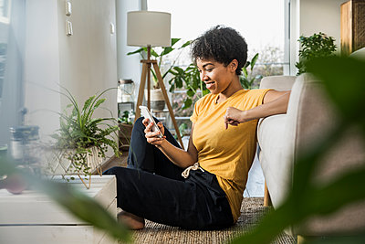 Woman smiling while using mobile phone sitting at home - p300m2244143 by Uwe Umstätter
