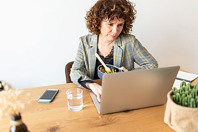 Female freelancer using laptop while holding food bowl on table at home - p300m2282268 by Sus Pons
