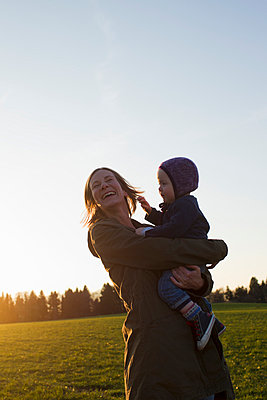 Mature mother and baby daughter laughing in field at sunset - p429m958570f by Christine Schneider