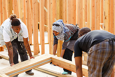 Volunteers lifting wooden frame at construction site - p555m1522805 by Roberto Westbrook