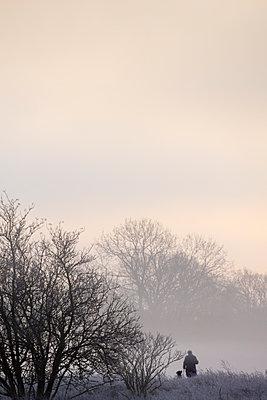 Mensch mit Hund im winterlichen Frühnebel - p739m1083911 von Baertels